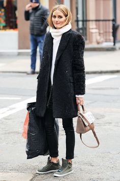 Olivia Palermo wears a white turtleneck with a textured coat, skinny pants, high-top sneakers, and a top-handle bag