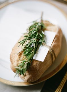 Calligraphy place card tied to rustic bread with twine and rosemary on place setting of gold-rimmed china and gold flatware. Place card by Oh My Deer, image by Austin Gros. #wedding