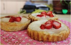 Some tarts with sweet cheese filling and strawberries
