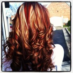 Curly brown hair with red and white highlights..