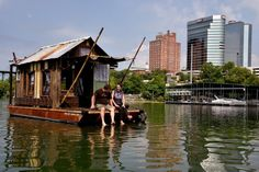 """Docked at Volunteer Landing at Knoxville's downtown waterfront this week is a 20-foot """"shantyboat"""" that looks all the world like a backwoods cabin perched atop a barge."""