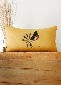 mustard pillow with birdy silhouette