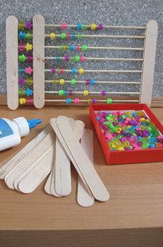 DIY abacus using large flat lolly sticks for the frame, thin round lolly sticks for the rods and pony beads to count with