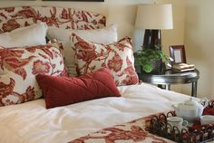 Different materials in a room make it more interesting. A metal nightstand keeps the red floral bedding from feeling too flirty, while a small plant and lamp with a modern silhouette pack a boho-chic punch.  - GoodHousekeeping.com