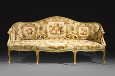 AN IMPORTANT PAIR OF GEORGE III GILTWOOD SOFAS  CIRCA 1770 each serpentine leaf-molded cresting rail centered by a stylized shell above an upholstered backrest flanked by upholstered sides, the upholstered armrests continuing to scrolled handholds on cabriole supports, the serpentine-fronted seat carved with gadrooned molding and centered between each leg with a stylized shell, raised on leaf-carved and gadrooned molded cabriole legs.  The whole upholstered with 19th century  needlework.