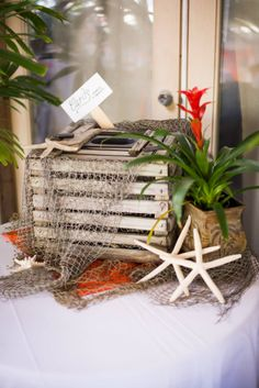Lobster trap with starfish and netting as a card holder for outdoor beach wedding. Photo taken by Caterson Media caterson.com at Coconut Cove Resort in Islamorada, FL