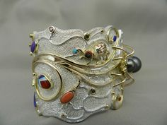 Jesse Monongya - This tufa-cast sterling silver bracelet also has lapis, Orange Sun Kiss and Ox Blood coral, Sleeping Beauty turquoise, Sugelite and dolomite. The Widow, watermelon but stems of the flowers are 18K yellow gold overlay.