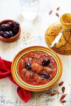 Tajine de merguez aux olives - 10 merguez de boeuf (ou boeuf mouton), 800 g de tomates en boîte concassées ou 3 tomates fraîches mûres concassées, 16 olives noires, 10 feuilles de persil plat hachées finement, 8 feuilles de coriandre fraîche, 1 oignon finement haché, 2 gousses d'ail hachées, 1 piment oiseau coupé en 2 et épépiné, épices (1 cc de cumin, 2 cc de coriandre en poudre, 1 cc de paprika, 1 pincée de gingembre en poudre), 6 cs d'huile d'olive vierge extra, sel.