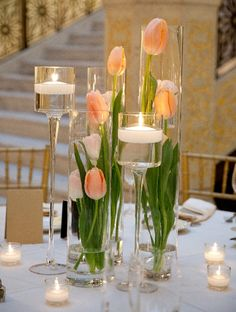Cylinder vases, tulips, and floating candles maek for an elegant and romantic centerpiece