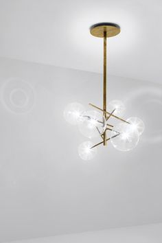 Balance and special effects in the hanging lamp with halogen point light (120 Watt). Transparent blown glass balls. Metal parts in hand burnished brass. The hand burnished brass finish looks naturally…
