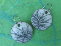 white torch fired enamel earrings with flower drawing and