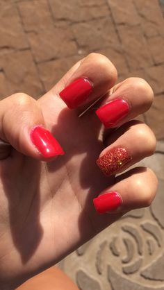 Square red nails w a red sparkle on my ring finger
