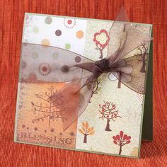 Send your seasons greetings by using various scrapbooking papers to create one look, then tie the it together with a ribbon. SOURCES Paper: Bazzill Basics Paper (Leapfrog), BasicGrey (Equinox), Juicy, Deciduous). Stamps: Fiskars, Heidi Grace Designs (We Are Family). Ink: Stewart Superior Palette (Burnt Umber). Ribbon: May Arts (1-1/2 inch sheer brown)./