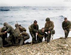 Medics from the 5th and 6th Special Engineer Brigade help wounded soldiers on Omaha beach, Fox Green and Easy Red sectors. Survivors of sunken landing craft are recovered by other troops, who reached the beach by using a life raft. June 6th, 1944, D-Day.