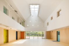 Hangdong Kindergarten,© Kyungsub Shin kindergarten, entry, skylight, wood wall panels, colored doors, steel guard railing