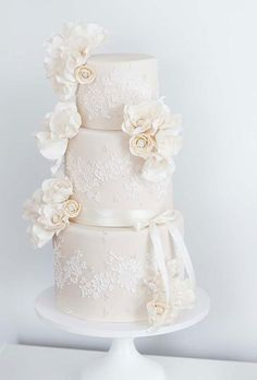 Three-Tier Wedding Cake with Ivory Fondant and Lace Pattern, Piping, and Pearls. This chic wedding cake by City View Bakehouse features tiers covered in ivory fondant; the lace pattern was created by using a cake stencil with added piping and pearls.