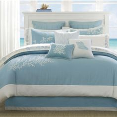 Coastline Coastal Themed Bedding Set - It's filled with Whites and Blues and it has Coral on the Bedding and Pillows.  Check out this bedding set and more in our ultimate guide to beach themed bedding sets!