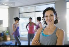 Portrait of smiling woman in yoga classroom - stock photo
