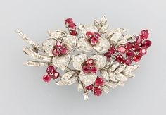 18 kt gold brooch with rubies and diamonds, WG 750/000, floral, representation of a flowerbouquet, 31 round-, oval- and pear shaped bevelled rubies total approx. 6 ct, brilliantsand diamond baguettes and -triangels total approx. 3 ct Wesselton/si-p1, complicated hand-made, approx. 4 x 7 cm, approx. 24.9 g  Estimation : 1.690€