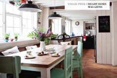 banquette table, painted chairs, open room... this is what I had in mind for cabin expansion.  Country kitchen in Heart Home Mag Photography by Emma Lewis