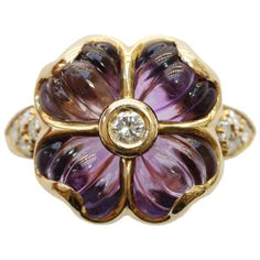 Boucheron Amethyst Diamond Flower Ring. An 18 carat gold ring in the shape of a flower with birlliant cut diamonds in the shank and at the heart of the flower, the petals are carved amethysts, signed and numbered: Boucheron, France circa 1980.