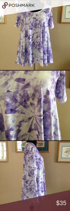 Lularoe perfect tee Lularoe purple and white kaleidoscope perfect tee. This is brand new but the tags are not attached. I bought off of eBay but did not realize it would smell like smoke when I received it. It had brand new tags attached but I took them off to wash and hang dry so this has never been worn. I let hang outside and in my laundry room for about 2 weeks and I think the smell is gone. LuLaRoe Tops Tees - Short Sleeve