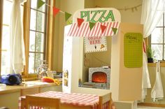 Folding poster board pizza storefront and construction paper banner. Fabric from fabric warehouse.