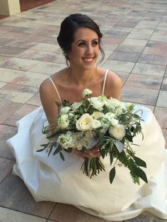 a beautiful bride holds her loosely tied, organic and lush white bridal bouquet of bridal bouquet of  white patience garden rose, white ranunculus, vendela rose, white majolik spray rose, white almond bloom, white scabiosa, dusty miller, seeded eucalyptus, fern, mondial rose & white stock wrapped in cream satin ribbon.
