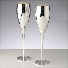 "Toasting Flutes - Silver Flutes - WeddingDepot.com - 002-89019 These highly-polished toasting glasses offer a simply design while accenting you cake knife or head table's flatware. Glasses stand 10"" tall with the bowl measuring 4"" tall x 2.25"" wide."