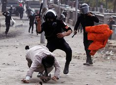 Riot police beat a protester opposing Egyptian President Mohamed Morsi during clashes along Qasr Al Nil bridge, which leads to Tahrir Square