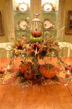 A cage atop a cake stand layered with miniature pumpkins and flowers