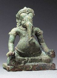 A Small Bronze Figure of Ganesha Khmer, Bayon Style, 12th/13th Century Seated on a rectangular plinth with coiled trunk wearing a sampot with butterfly sash at rear, armlets, necklace and conical headdress 3¼ in. (8.4 cm.) high