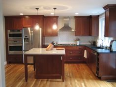 Cherry Kitchen Cabinets Buying Guide wood cabinets with wood floors Cherry Wood Kitchen Cabinets, Cherry Wood Kitchens, Backsplash With Dark Cabinets, Wood Floor Kitchen, Brown Cabinets, Kitchen Worktop, Kitchen Backsplash, Soapstone Counters, Kitchen Floors