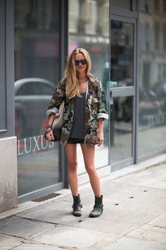 Try pairing a hunter green camouflage military jacket with black denim shorts for a casual level of dress. Polish off the ensemble with black leather booties.   Shop this look on Lookastic: https://lookastic.com/women/looks/military-jacket-crew-neck-t-shirt-shorts/17858   — Dark Green Camouflage Military Jacket  — Charcoal Crew-neck T-shirt  — Charcoal Canvas Tote Bag  — Black Denim Shorts  — Black Leather Ankle Boots  — Black Sunglasses