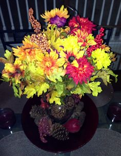 A fall inspired flower arrangement with fake flowers.