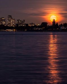 Midnight Sun   The moon rises over Kitsilano and reflects off the waters of English Bay. This was the evening after the Sturgeon Moon (waning gibbous) On the left the lifeguard station and the Boathouse restaurant on Kits Beach. Captured from the Jericho Pier Vancouver British Columbia Canada  August 19 2016