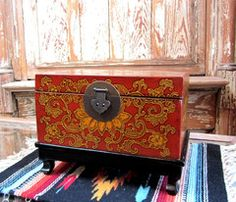 Chinese jewelry box, red stencil pattern on a black wooden stand.