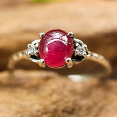 Ruby oval cabochon ring with diamond side set gems in prongs setting with sterling silver texture hammer band