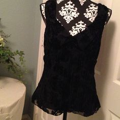 Cute black crinkle top w/velvety flowers!! This cute black top is sleeveless and zips on the side. It is a crinkly fabric with velvety flowers. Tops