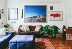 Sala de estar com parede de tijolinho pintado de branco, tapete étnico e sofás em cores neutras.