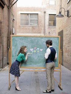 """Chalkboard in an ally way, bride-to-be in a flirty polka dot skirt. Vest and oxford shoes for him. Great save the date photo! Wrap It Up Pretty 