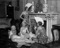 December, 1927: a group of girls dressed as fish for the Chelsea Arts Ball have a cup of tea before the festivities.