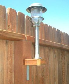 """Solar lights aren't just for the ground! Take a 2x4 and cut them into squares to fit the existing fence posts. Using galvanized screws - not nails - to screw a """"L"""" bracket to the underneath base. Then on top, screw on the stake.  I am going to do this for the kids Rainbow playset!"""