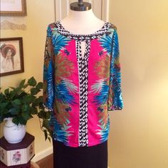 Nicole Miller Cold Shoulder Tunic.  NWOT This is a really cute tunic top by Nicole for Nicole Miller in a size medium. Key hole notch at front neckline. Open shoulders. 3/4 sleeves. Beautiful tropical print in pink, blue, green with black and white border print. Great for vacations in the sun or for a cruise. NWOT Nicole by Nicole Miller Tops Tunics