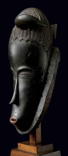 Masque Gouro. Une face très étroite et allongée se coiffe curieusement d'une feuille au contour festonné, dont la tige se courbe droite, comme une corne. C'est un chef d'oeuvre de l'art noir !