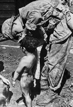 An American Marine gives care to a Japanese civilian boy on Saipan.  While the Japanese army was brutal to both soldiers and civilians alike, Americans treated those captured with kindness (June-July 1944)