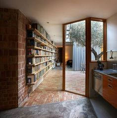 This simple wooden bookshelf lines the wall separating indoor space from a courtyard. What a stunning way to transition between the two!