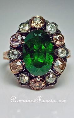"A Russian Demantoid Garnet and Fancy Colored Diamond Cluster Ring  circa 1890, with a later shank  The ring is set with an exceedingly rare 5.1 carat Russian Ural demantoid, encircled by a single row of six white and six fancy colored old cut diamonds with an approximate total weight of 1.80 ct.  The dark grass green stone is full of 'valuable' so-called ""horsetails"",  inclusions found only in demantoids from the Urals."