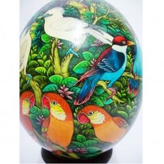 Largest of eggs. Colorful hand painted empty ostrich egg shell. Hand carved wooden stand specifically made to fit the egg shell. Theme of the drawing is -Colorful birds in the forest.US$173.00