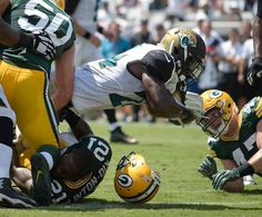 Jacksonville Jaguars running back T.J. Yeldon dives over the goal line past Green Bay Packers inside linebacker Blake Martinez (50) and free safety Ha Ha Clinton-Dix (21) for a touchdown during the first half of an NFL football game in Jacksonville, Fla., Sunday, Sept. 11, 2016.